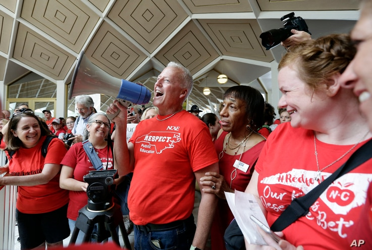 FILE -- Mark Jewell, president of the North Carolina Association of Educators asks teachers to refrain from chanting and causing a disturbance outside the House and Senate chambers during a teachers rally at the General Assembly in Raleigh, N.C., May...