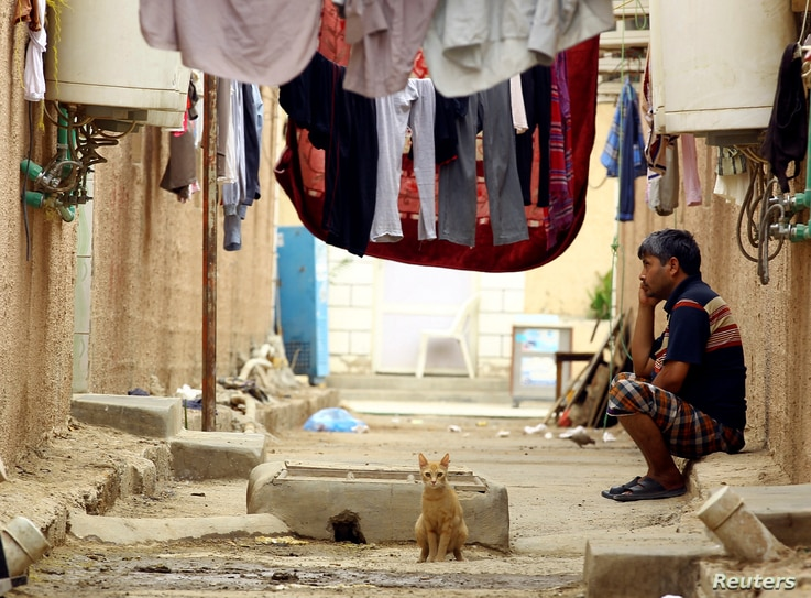 A cat sits near an Asian worker at his accommodation in Qadisiya labor camp, Saudi Arabia, Aug. 17, 2016.