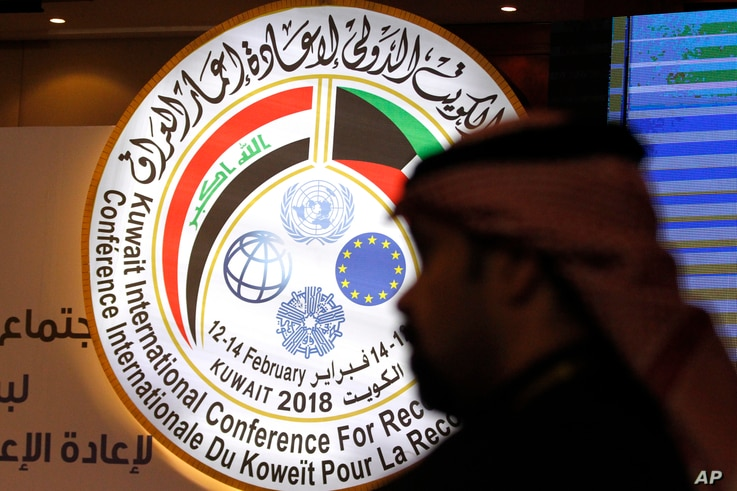 A Kuwaiti official stands in front of an illuminated sign for a conference on Iraq being held in Kuwait City, Kuwait, Feb. 12, 2018.