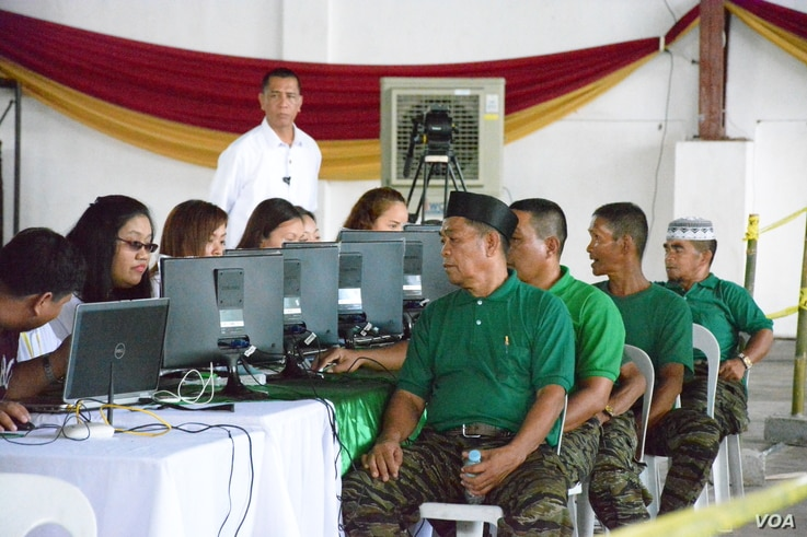 Jacob Palao (wearing black cap), a rebel deputy commander, gets processed for livelihood assistance at the decommissioning ceremony for Moro Islamic Liberation Front fighters who are being integrated into society, in Sultan Kudarat, Maguindanao Provi...