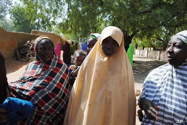 Falmata Abubakar, center, one of the kidnapped girls from the Government Girls Science and Technical College Dapchi who was freed, is photographed after her release,  in Dapchi, Nigeria, March. 21, 2018.