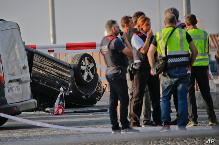Police officers speak near an overturned car at the spot where terrorists were intercepted by police in Cambrils, Spain, Aug. 18, 2017. The police force for Spain's Catalonia region says the five suspects shot and killed in the resort town of Cambril...