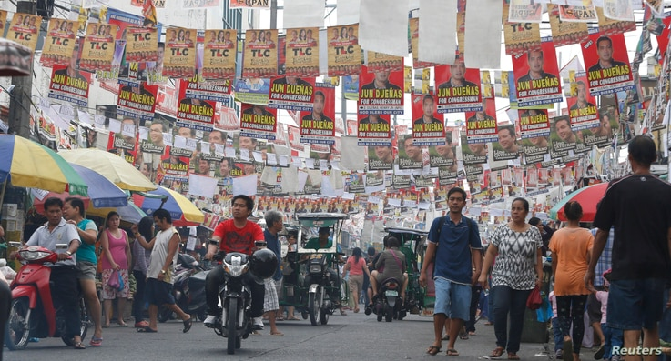 Election posters for the midterm elections hang along a street as residents walk to a polling precinct in Taguig, Metro Manila May 13, 2013. More than 50 million Filipinos will cast their votes for a new set of lawmakers and local officials on Monday...