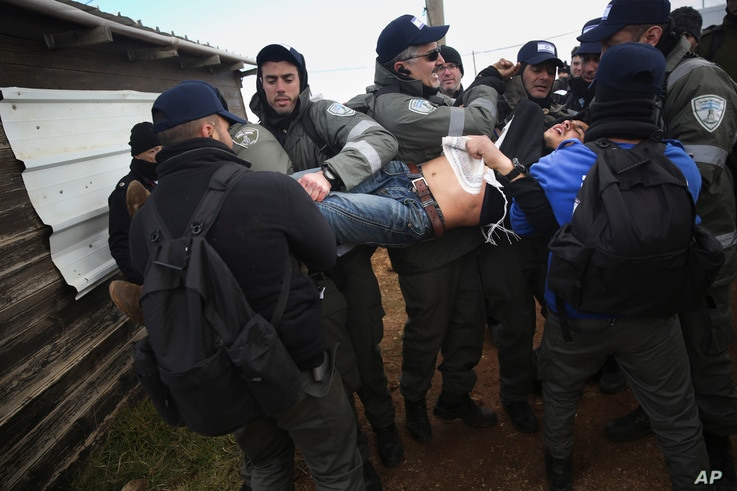 Israeli police arrest a settler in the West Bank outpost of Amona, Feb. 1, 2017.