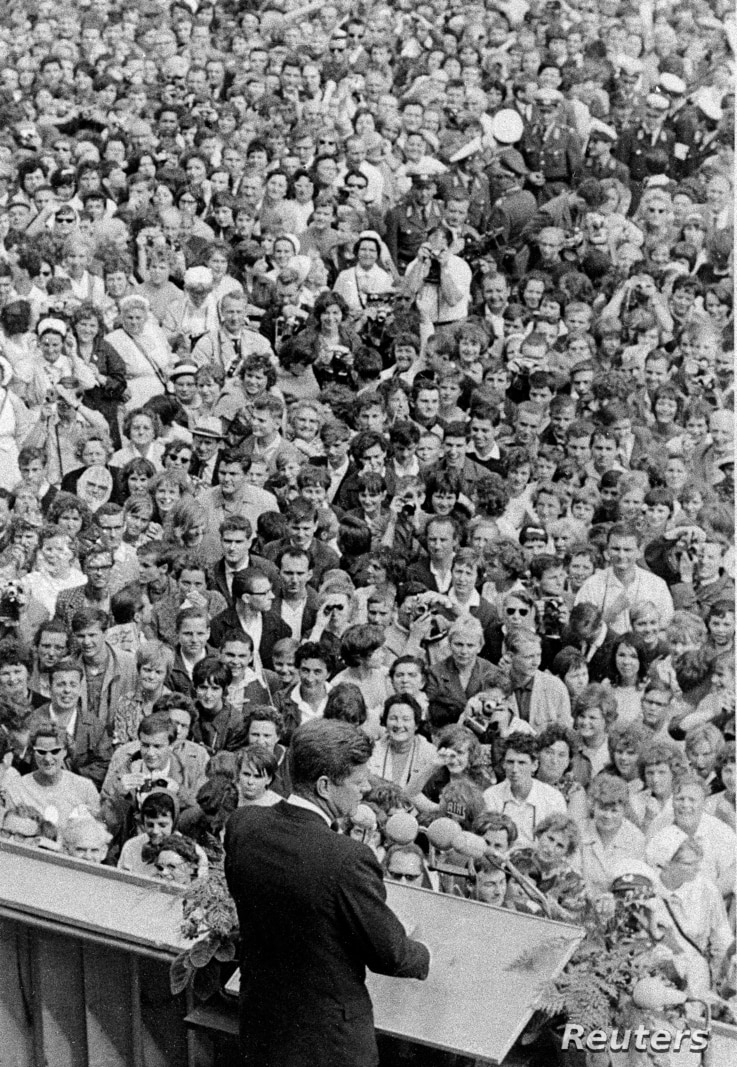 U.S. President John F. Kennedy, standing on rostrum, addresses a large crowd in the main square in front of Schoeneberg City Hall in West Berlin, Germany, June 26, 1963.