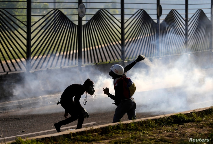 Opposition supporters throw stones into an air base while clashing  with riot security forces during a rally against President Nicolas Maduro in Caracas, Venezuela, May 18, 2017.