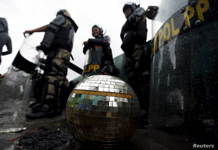 FILE - A disco ball rests near civil service police unit members as buildings are demolished at Kalijodo red-light district in Jakarta, Indonesia, Feb. 29, 2016.