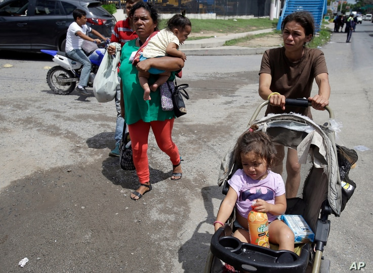 A couple of Honduran migrant mothers carry their children as they continue on their trek to the United States, in Teculutan, Guatemala, Oct. 17, 2018.