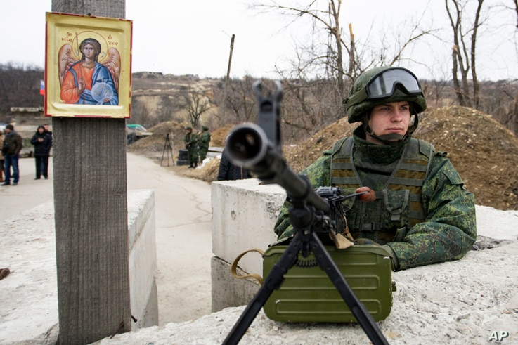 FILE - A separatist rebel guards a check point at the village of Luhanska, Ukraine, March 7, 2017.