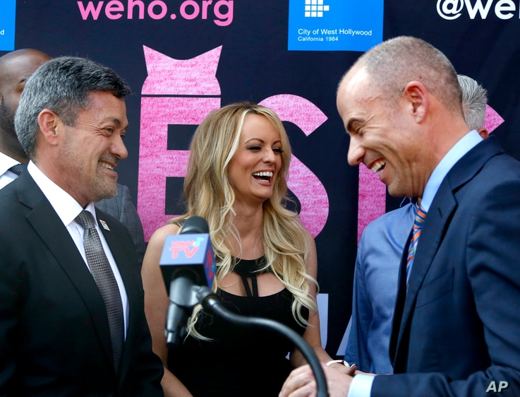 West Hollywood Mayor John Duran, left, Stormy Daniels, center, and attorney Michael Avenatti attend a ceremony for Daniels at which she received a ceremonial key to the city, May 23, 2018, in West Hollywood, Calif.