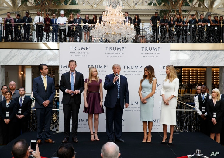 FILE - Then-candidate Donald Trump, accompanied by his family, speaks during the grand opening of the Trump International Hotel-Old Post Office, Washington, Oct. 26, 2016. Experts on government ethics are warning President-elect Trump that he'll neve