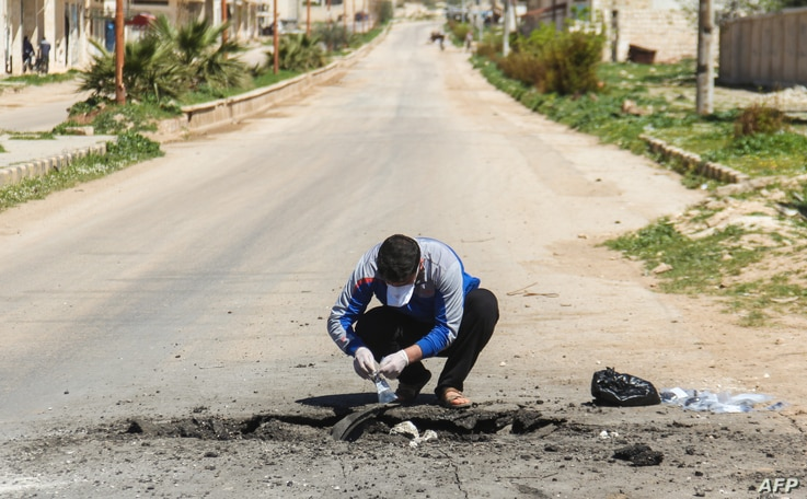 A Syrian man collects samples from the site of a suspected toxic gas attack in Khan Sheikhun, in Syria's northwestern Idlib province, April 5, 2017.