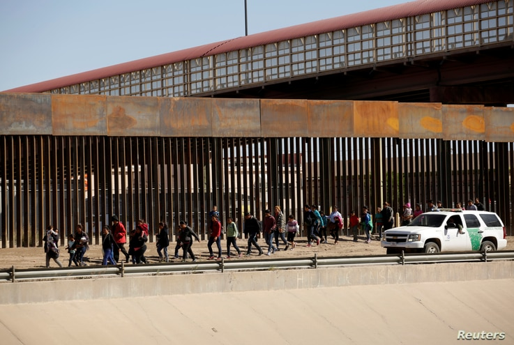 Migrants are escorted by U.S. Customs and Border Protection officials after crossing illegally into the United States to request asylum, in El Paso, Texas, in this picture taken from Ciudad Juarez, Mexico, April 3, 2019.