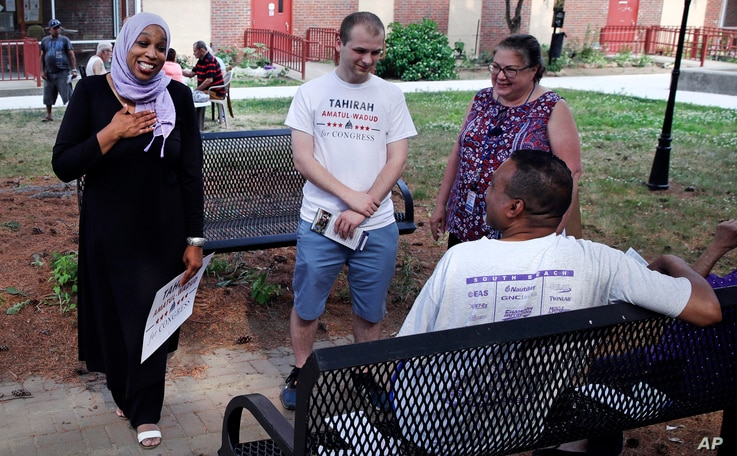 In this Monday, June 18, 2018, photo, attorney Tahirah Amatul-Wadud, left, who is challenging incumbent U.S. Rep. Richard Neal, D-Mass., greets residents of an apartment complex while campaigning in Springfield, Mass.