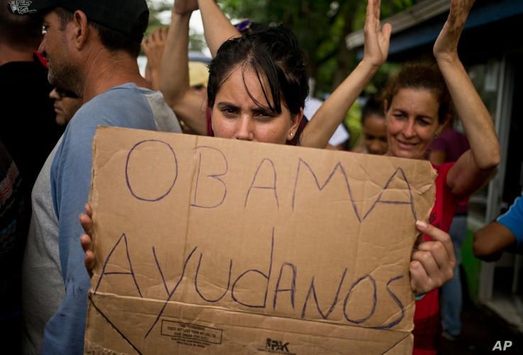 """FILE - A Cuban migrant holds a sign that reads in Spanish """"Help us Obama"""" during a protest at the Costa Rican border with Nicaragua, Nov. 16, 2015."""