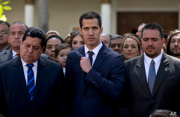 Lawmakers Juan Guaido, center, President of National Assembly, Edgar Zambrano, left, first Vice President and Stalin Gonzalez, right, second Vice President pose after being sworn in during a special session at the National Assembly in Caracas, Venezu...