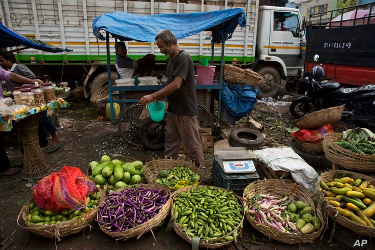 A vegetable seller sprinkles water on vegetables to stop them from drying out at a market in Gauhati, India on June 16, 2016.