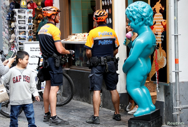 Belgian police officers are seen next to a replica of Brussels' iconic Manneken Pis statue during a patrol in central Brussels, Belgium, May 31, 2017.