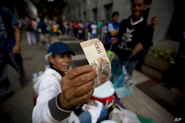 A street vendor inspects the authenticity of a 100-bolivar note as people stand in line outside a bank to deposit their bank 100-bolivar bank notes, in Caracas, Venezuela, Dec. 13, 2016.