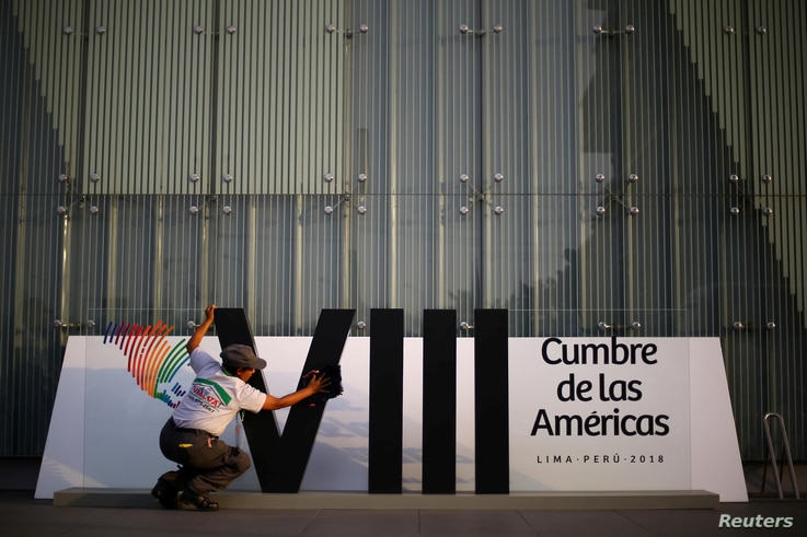 A woman cleans a banner ahead of the 8th Summit of the Americas in Lima, Peru, April 10, 2018.