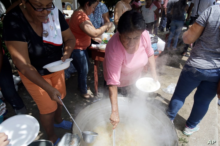 Honduran migrants who are traveling to the United States as a group get food from a a group of volunteers in Teculutan, Guatemala, Oct. 17, 2018.
