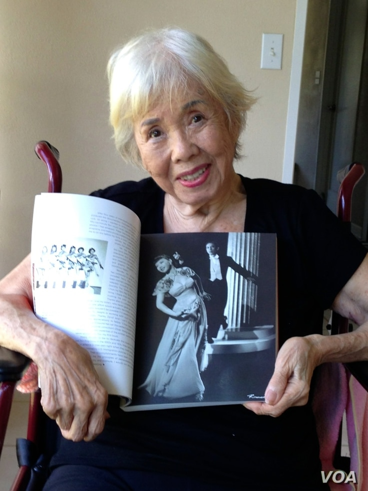 Dancer, actress and nightclub hostess Mai Tai Sing, now 91, shows a photo of her and her husband Wilber Tai Sing dancing at Forbidden City in 1942 (H. Chang/VOA).