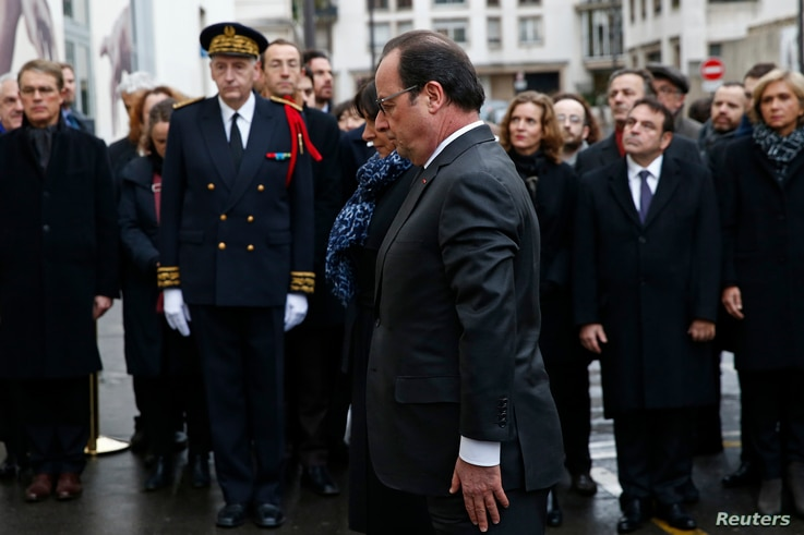 French President Francois Hollande (C) and Paris Mayor Anne Hidalgo attend a ceremony to unveil a commemorative plaque to pay tribute to the victims of the last year's January attacks outside the former offices of French weekly satirical newspaper Ch...