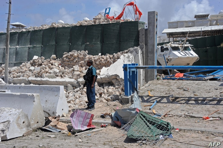 A Somali soldier stands next to a crumbled perimeter wall outside the UN's office in Mogadishu on July 26, 2016 following twin car bombings.