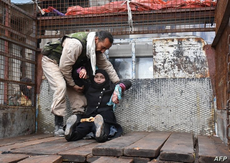 A wounded Syrian woman from the al-Sukari neighbourhood is helped onto the back of a truck as she flees during the ongoing government forces military operation to retake remaining rebel-held areas in the northern embattled city of Aleppo on December ...
