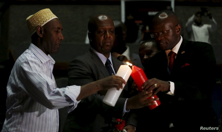 Kenya's National Counter Terrorism Center Director Martin Kimani, center, is assisted in lighting a candle during prayers to commemorate the first anniversary of the attack at the Garissa University College, in Kenya's capital, Nairobi, April 2, 2016...