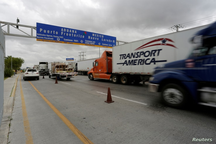 FILE -  Trucks wait in the queue for border customs control to cross into the U.S. at the World Trade Bridge in Nuevo Laredo, Mexico on Nov. 2, 2016.
