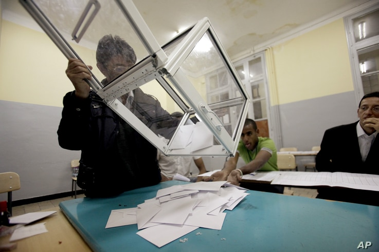 An election worker empties a ballot box to count votes after parliamentary elections at a polling station in Algiers May 10, 2012.