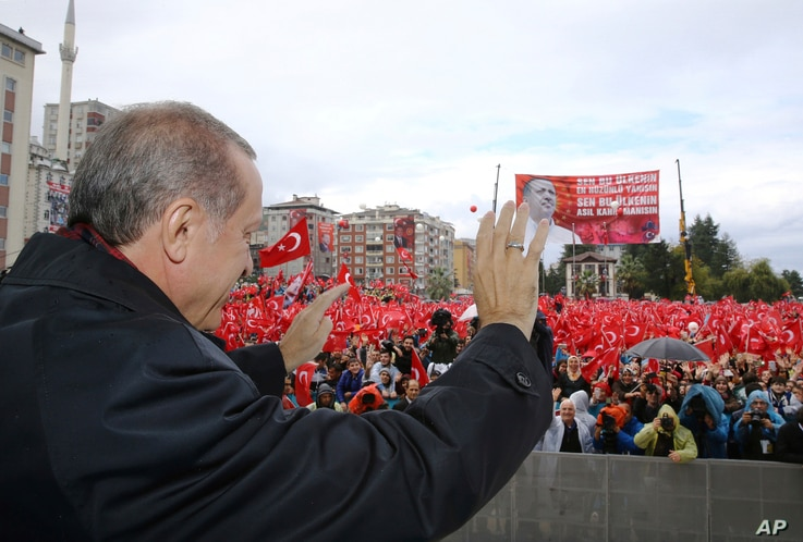 """Turkish President Recep Tayyip Erdogan salutes the crowd of supporters in his hometown of Rize, on the Black Sea coast of Turkey, Oct. 15, 2016. Erdogan said Turkey was moving into Dabiq, Syria, and would declare a """"terror-free safe zone"""" in the regi"""