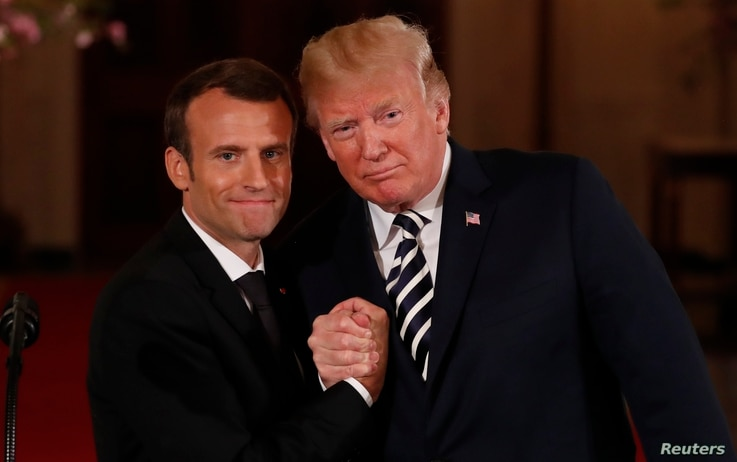 French President Emmanuel Macron clasps hands with U.S. President Donald Trump at the conclusion of their joint news conference in the East Room of the White House in Washington, U.S., April 24, 2018.