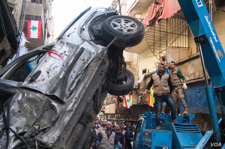 A crane lifts a car wrecked by one of the bombs. Many in the neighborhood said the attacks would not dampen their support for Hezbollah's military backing of the Syrian government.