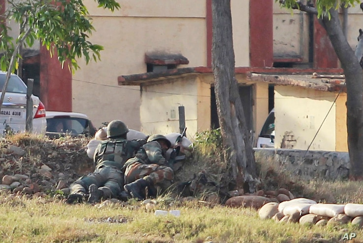 An Indian soldiers take position as they surround the residential quarters where militants are believed to be holed up in an Army camp in Jammu, India, Feb. 11, 2018.