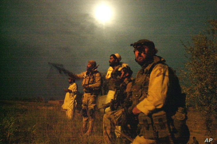 FILE - Members of the U.S. Army Special Forces watch the perimeter of a compound suspected of holding al-Qaida and Taliban forces during a raid.