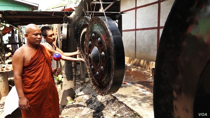 Panna Jota, who traveled 600 kilometers from Mon state to purchase a modest-sized gong at the Mandalay workshop, inspects a gong. (Z. Aung/VOA)
