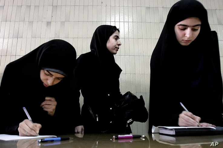 FILE -  Iranian students fill out registration forms indicating their readiness for martyrdom, or to carry out suicide attacks, in Tehran, Iran, Feb. 18, 2006.
