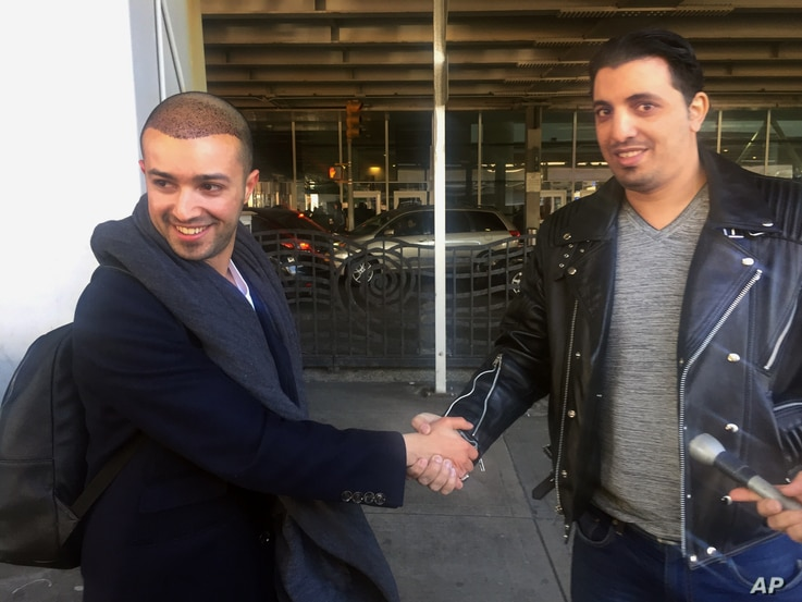 Ammar Alnajjar, left, shakes hands with his cousin, Fahd Alfakih, after coming into New York's JFK International Airport on a flight from Istanbul, Turkey, Feb. 4, 2017.