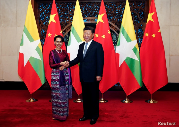 Myanmar State Counselor Aung San Suu Kyi, left, and Chinese Premier Xi Jinping greet the media before a meeting in Beijing, Aug. 19, 2016.