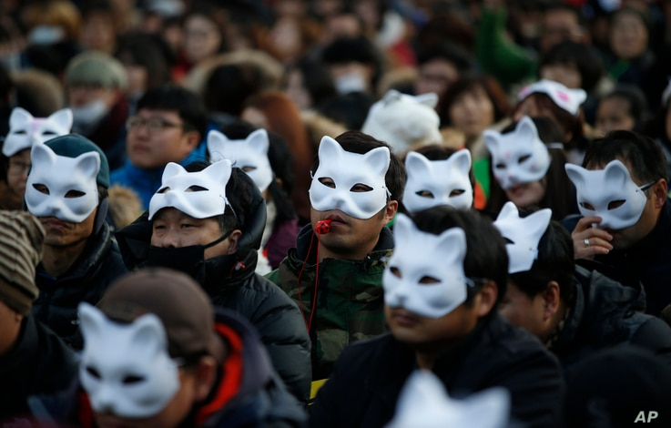 South Korean protesters wearing half masks attend an anti-government rally in downtown Seoul, South Korea, Dec. 19, 2015.