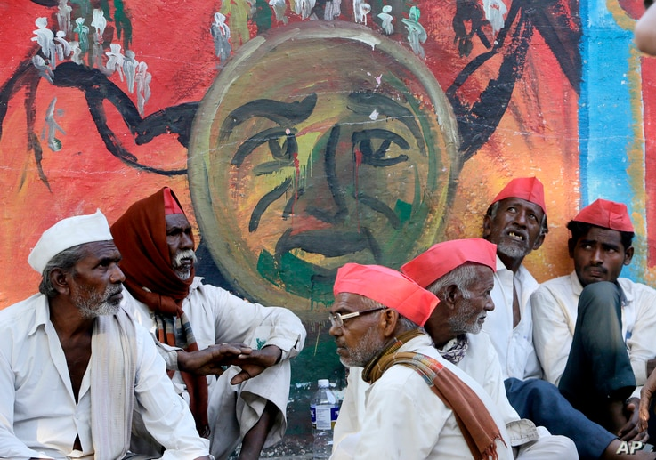 Indian farmers sit in front of a graffiti at the end of their six day long march on foot, in Mumbai, India, Monday, March 12, 2018.
