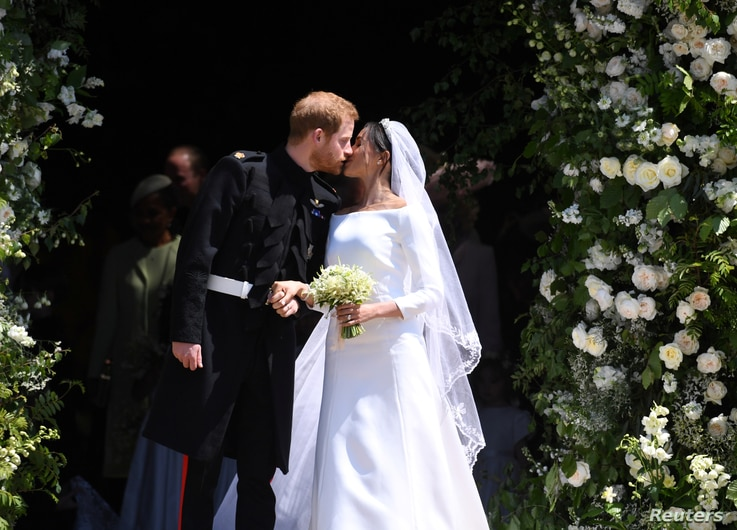Prince Harry and Meghan, the Duchess of Sussex, kiss as they leave St George's Chapel at Windsor Castle after their wedding, May 19, 2018.