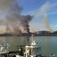 Picture taken by a South Korean tourist shows huge plumes of smoke rising from Yeonpyeong island in the disputed waters of the Yellow Sea on 23 Nov 2010
