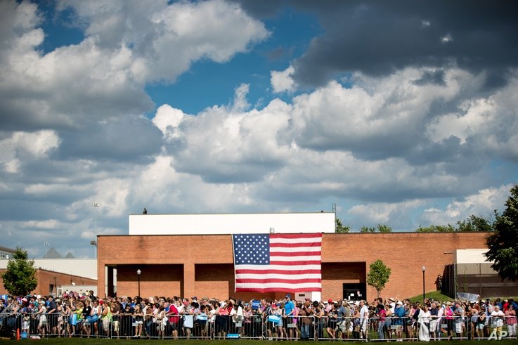Members of the audience stand in front of a large American flag as Democratic presidential candidate Hillary Clinton, accompanied by Democratic vice presidential candidate, Sen. Tim Kaine, D-Va., speaks at at rally at Fort Hayes Metropolitan Educatio...