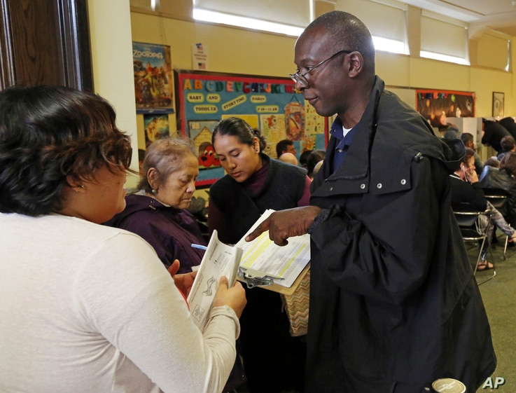 Poll worker Phillip George helps a voter check in at a weekend early voting polling place at the North Hollywood branch library in Los Angeles, Oct. 30, 2016