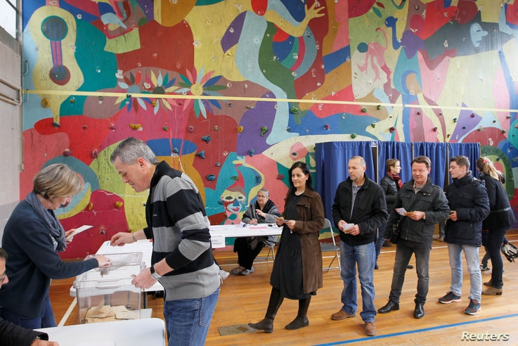 People wait in line to vote during the second round of 2017 French presidential election at a polling station in Bron, France, May 7, 2017.