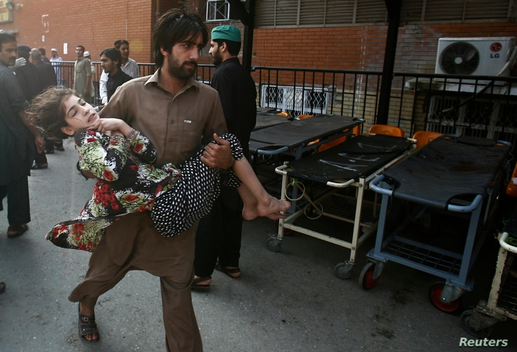 A man carries a girl, who was injured in a bomb blast, as she is brought to the Lady Reading Hospital for treatment in Peshawar, Oct. 7, 2013.