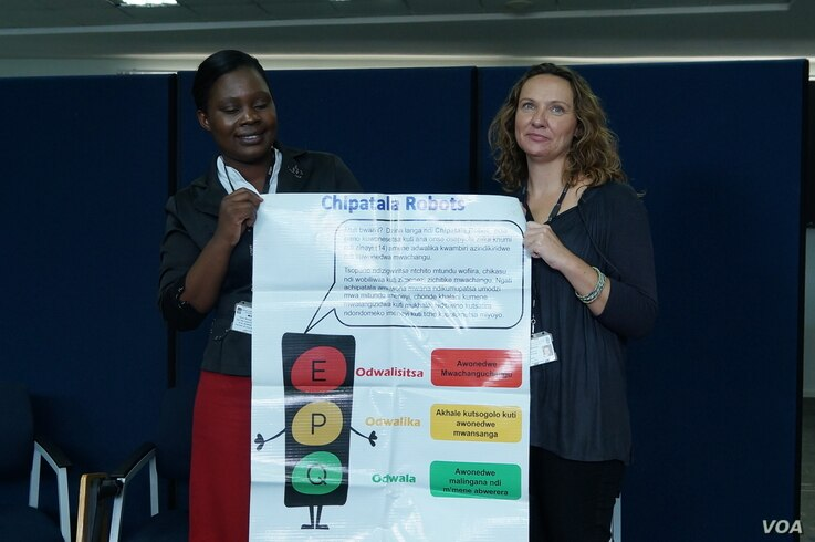 Mtisunge Mhango (left), program coordinator, and Nicola Desmond, a researcher at Malawi-Liverpool Welcome Trust, holding poster showing how Chipatala Robot program's colors work.